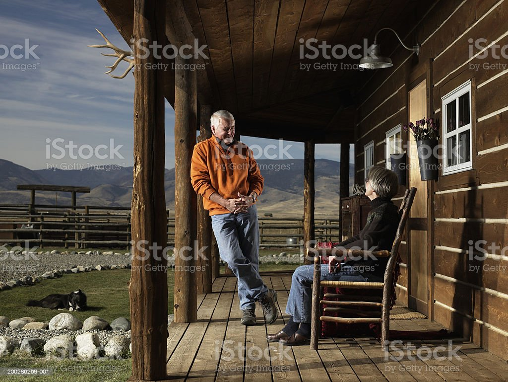 Senior man and woman having conversation on porch, smiling stock photo