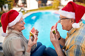 Happy senior man and woman in Santa hats enjoy on Christmas holiday and eating watermelon