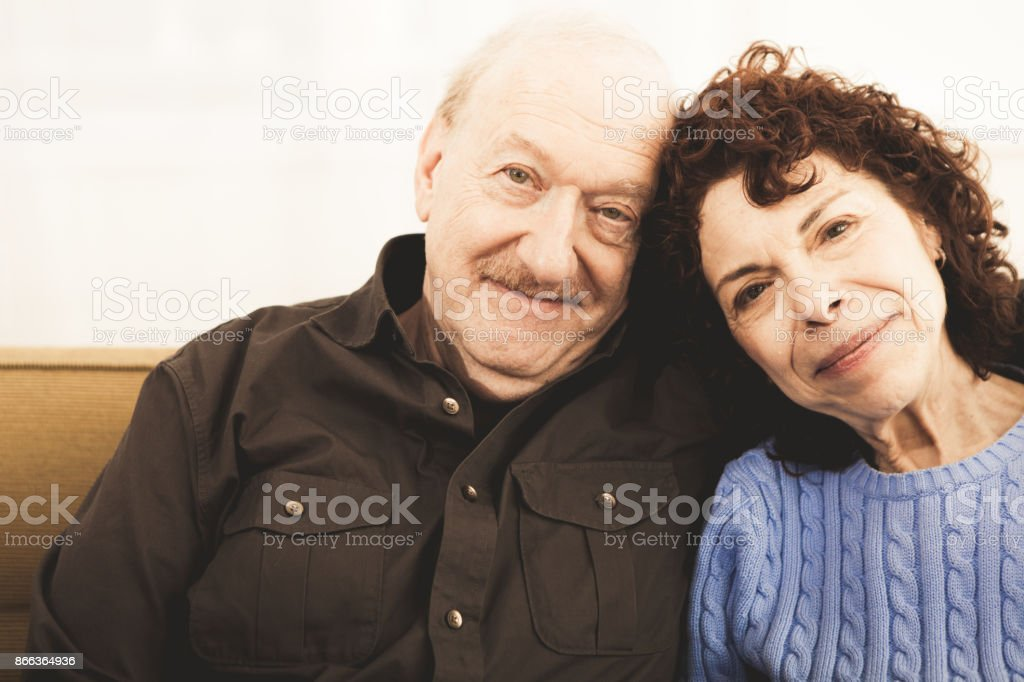 A senior man and woman having a moment of tenderness looking at the...