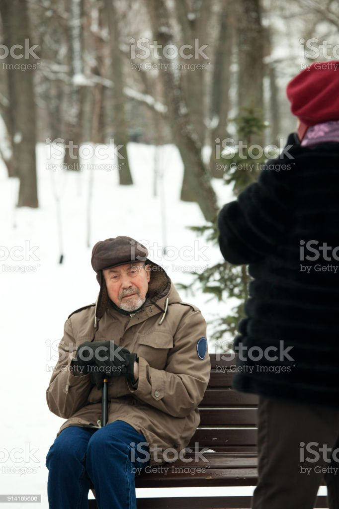 Senior man and woman on a walk in winter park stock photo