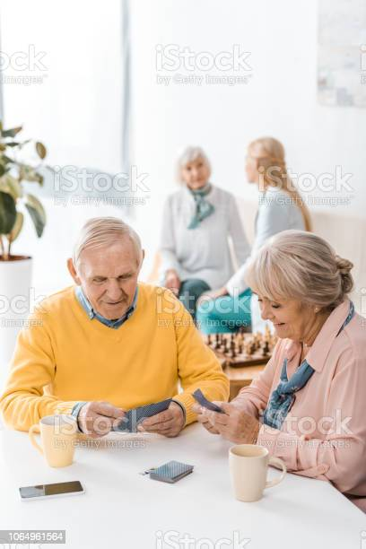 Senior man and woman playing cards at table at nursing home picture id1064961564?b=1&k=6&m=1064961564&s=612x612&h=pechsh7616g6u1owkf0 lo8h im4p5xuduh921qmohi=