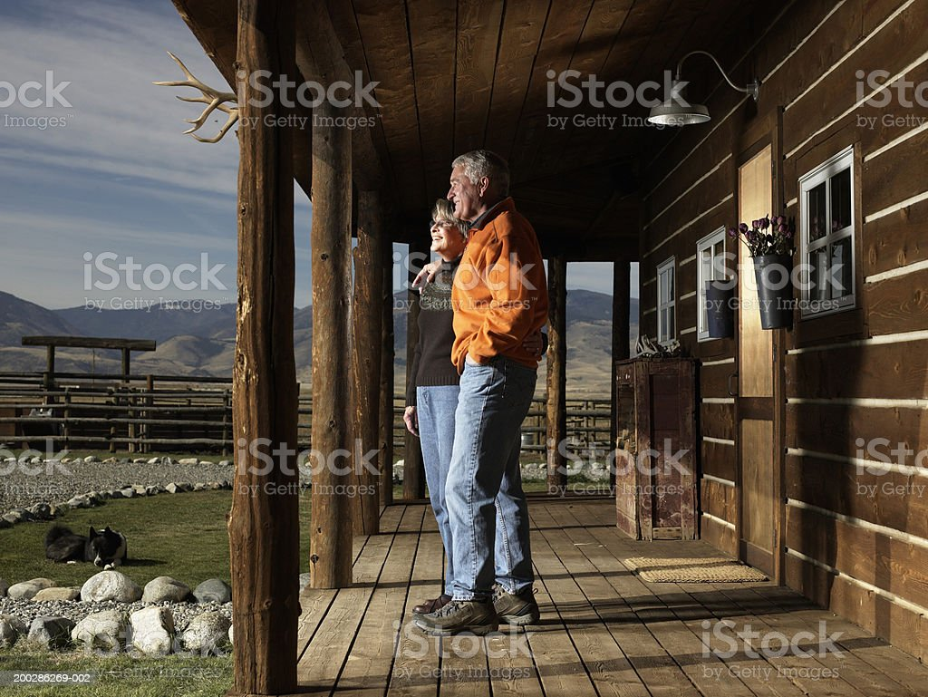 Senior man and woman standing on porch, embracing, side view stock photo