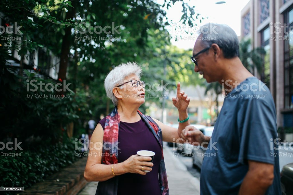 Senior man and woman talking on the street of Kuala Lumpur, Malaysia stock photo