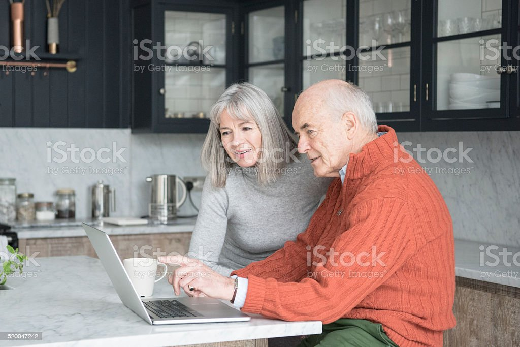 Senior man and woman using laptop at home together stock photo