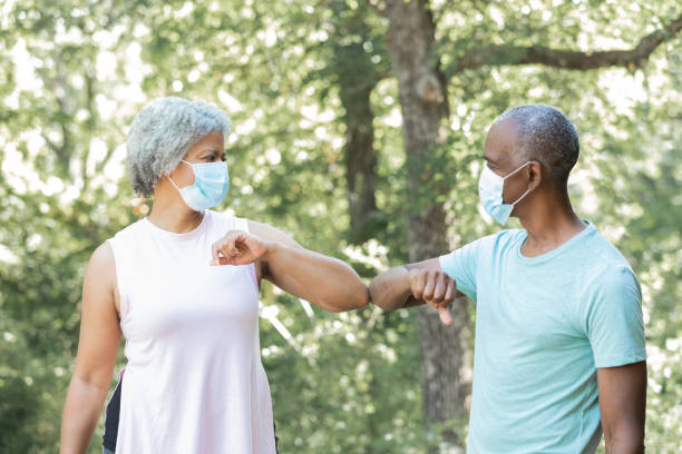 Senior man and woman wearing masks greet each other by touching elbows instead of shaking hands stock photo