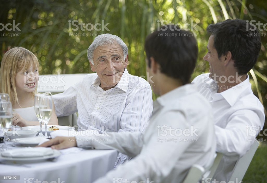 Senior man and young girl at outdoor party talking to two men and smiling royalty-free stock photo