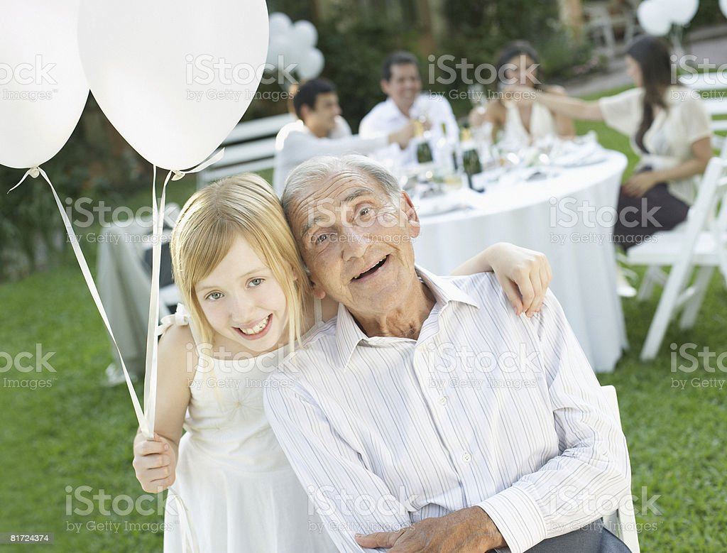Senior man and young girl at outdoor party with balloons smiling royalty-free stock photo
