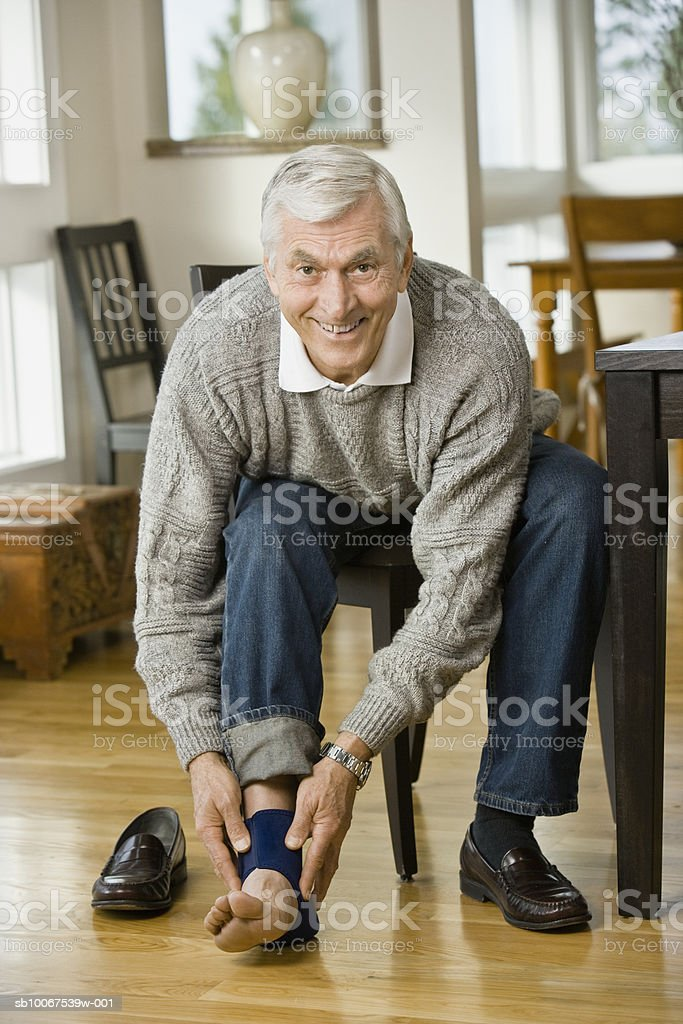 Senior man applying ankle brace, smiling, portrait foto de stock libre de derechos