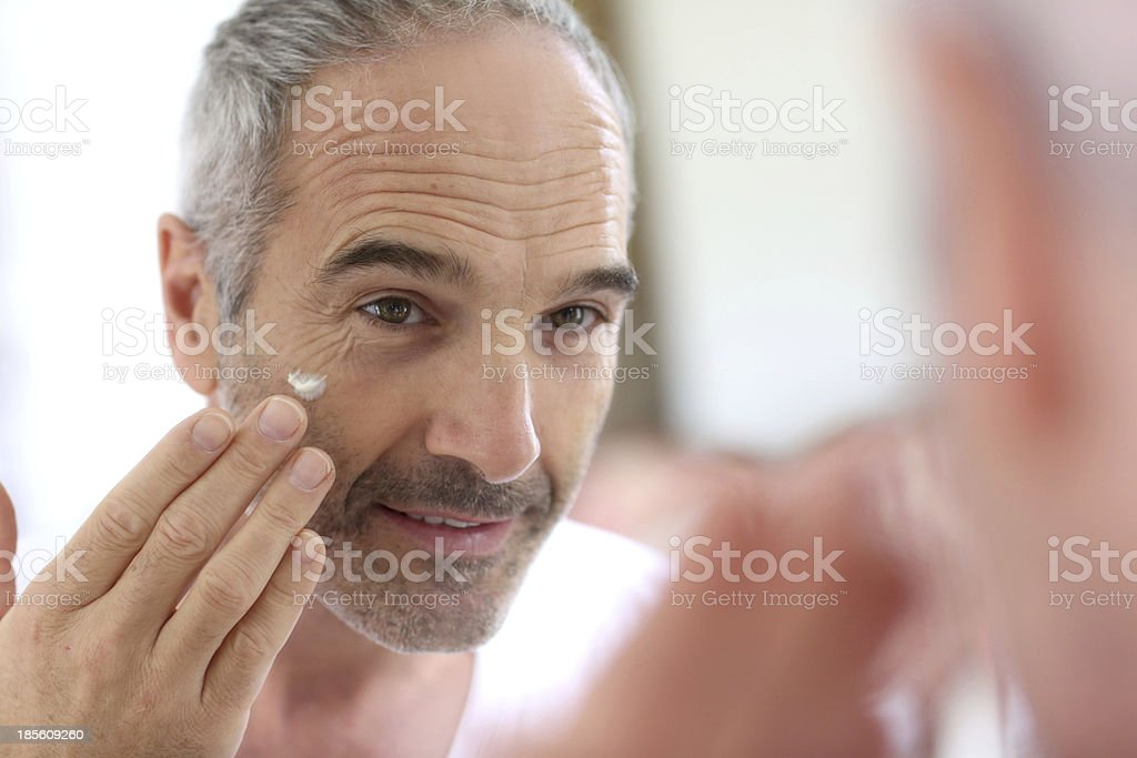 Alter Mann Anwendung der Creme im Badezimmer – Foto