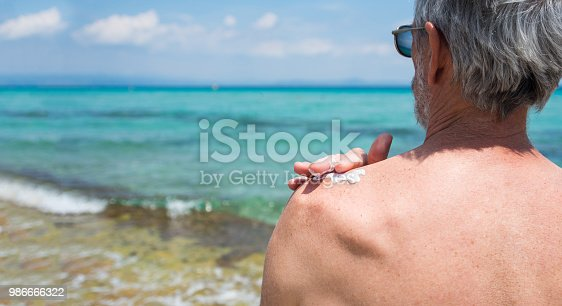 istock Senior man applying sun lotion on summer vacation 986666322