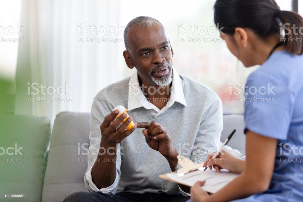 Senior man asks female homehealth nurse about medication - Royalty-free Adult Stock Photo