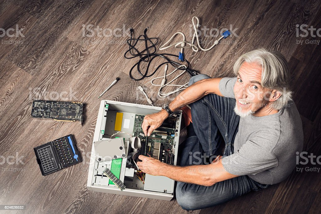 Senior man assembling a desktop computer stock photo