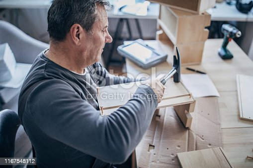 459069877 istock photo Senior man assembling furniture at home, a new home concept 1167548112