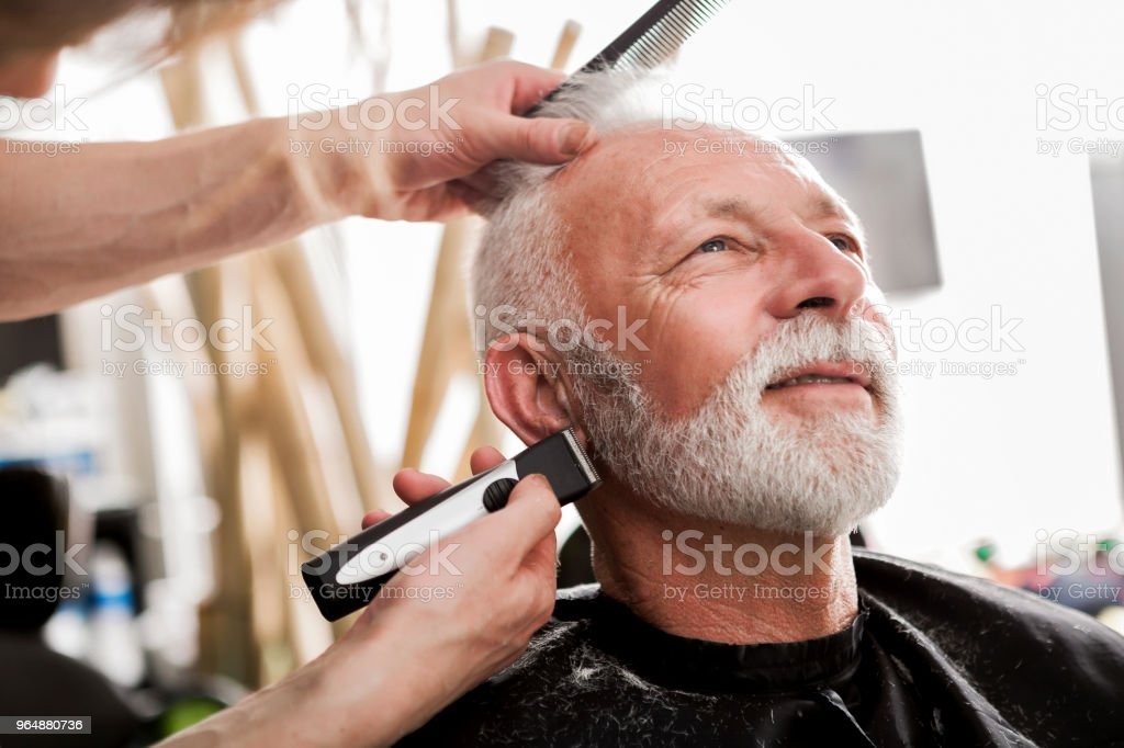 Senior man at a barber trimming beard royalty-free stock photo