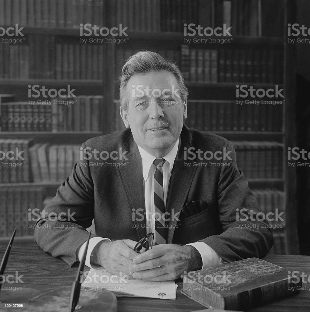Senior man at desk with bookshelf in background, portrait stock photo