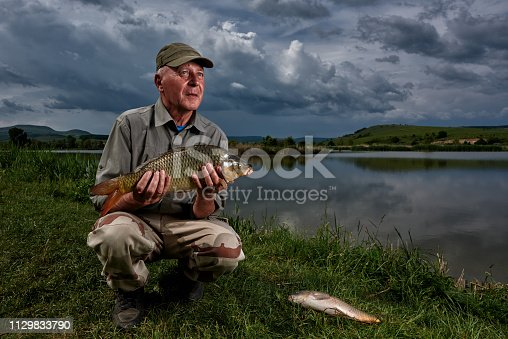 retirement lifestyle of senior man holding carp after fishing it.