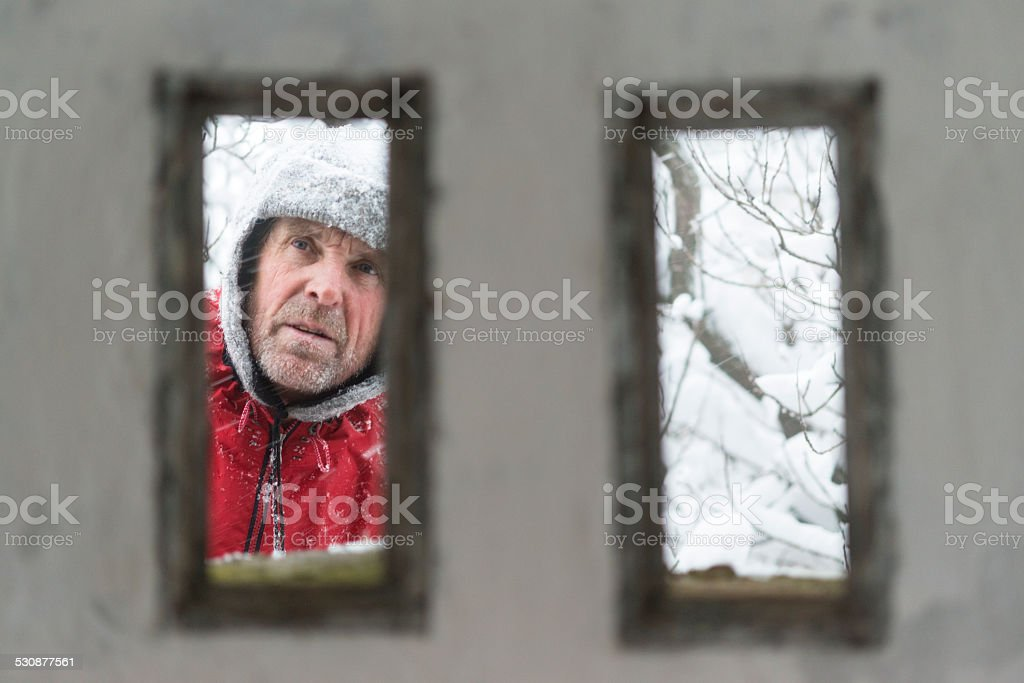 Senior Man at Great War's Bunker Porthole , Snowing, Alps, Europe stock photo