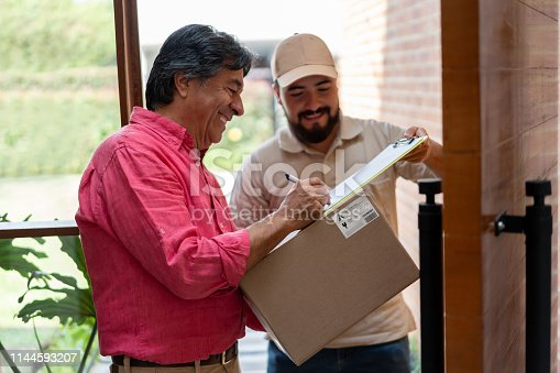 Senior man at home receiving a package and signing a document while postal worker holds clipboard smiling