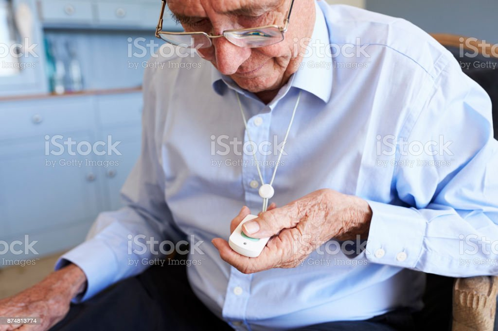 Senior Man At Home Using Distress Alarm Call Button - fotografia de stock