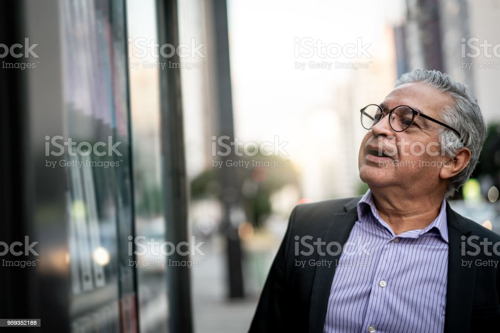 Senior Man at looking for store window stock photo