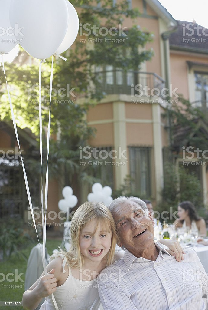 Senior man at outdoor party with young girl holding balloons and smiling royalty-free stock photo