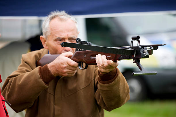 senior man at sports event - crossbow stock pictures, royalty-free photos & images