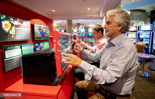 1032204252 istock photo Senior man at the casino sports betting using a screen 1032204176
