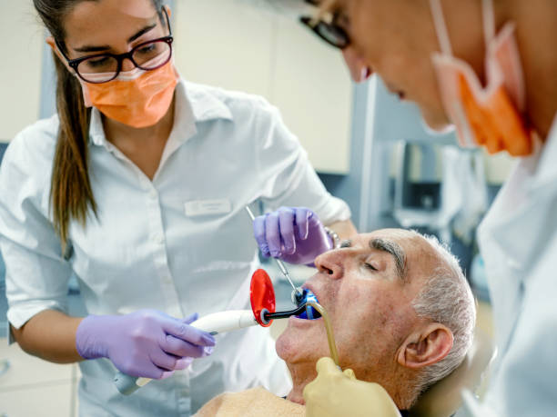 Senior man at the dentist Female dentist treating patient senior man teeth. tranquilizing stock pictures, royalty-free photos & images