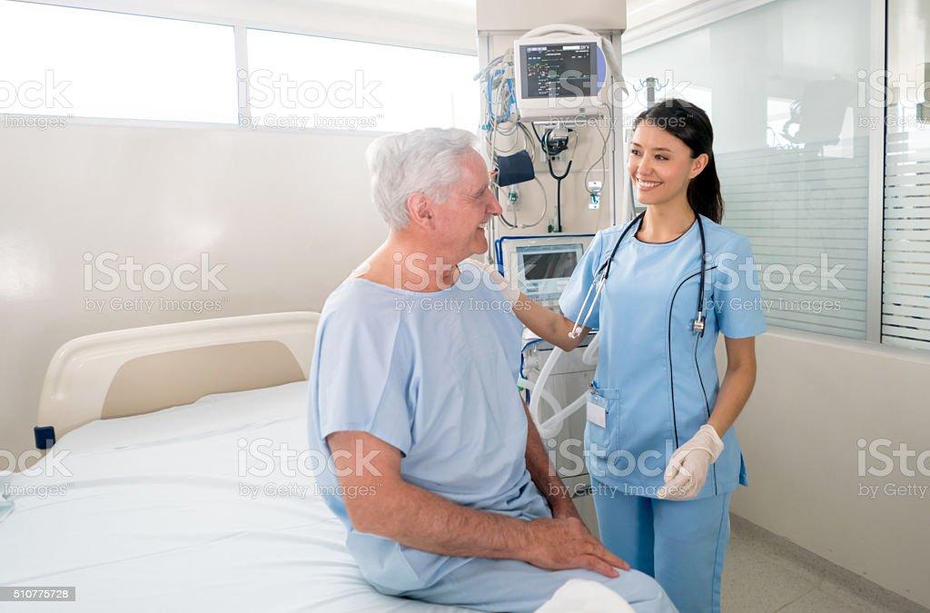 Senior man at the ICU talking to the nurse stock photo