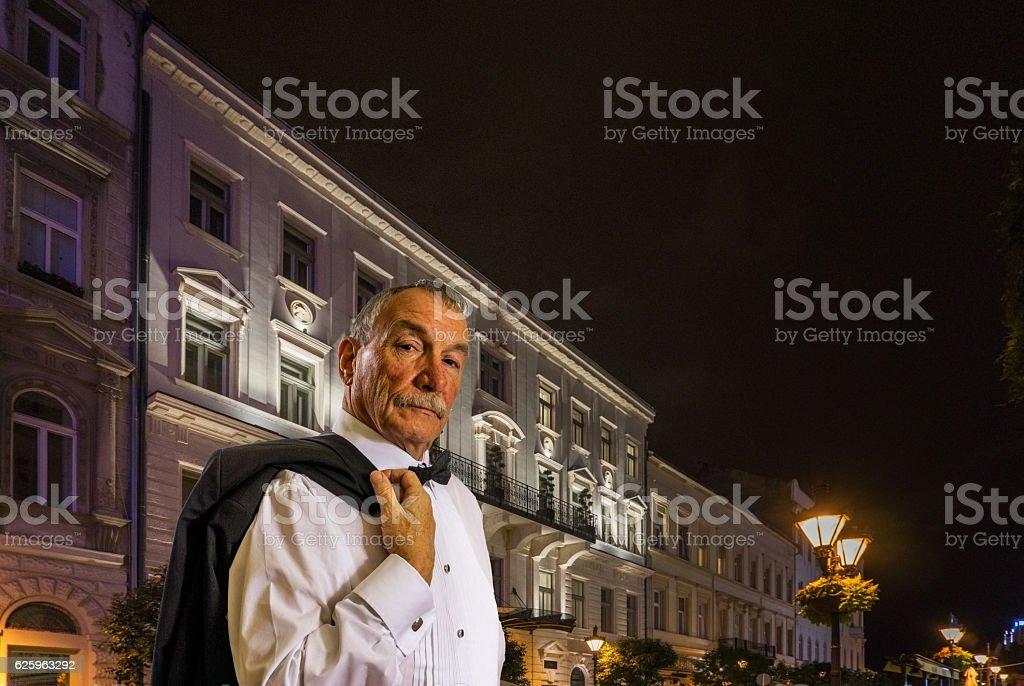 Senior man attending swish party in city at night stock photo
