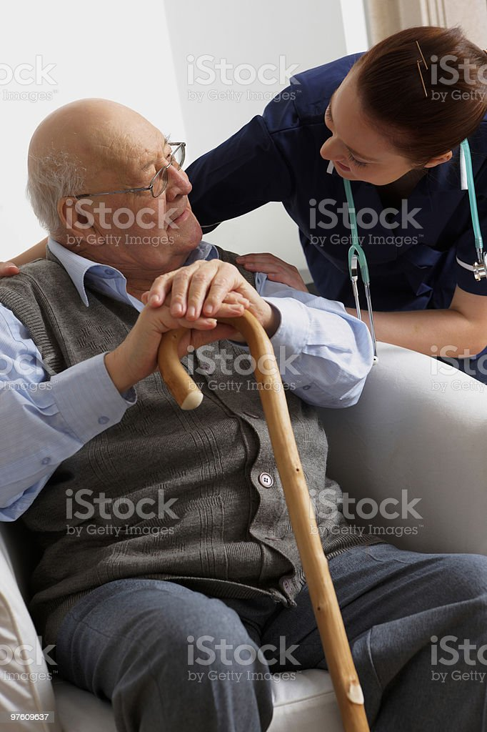 Senior man being visited by a nurse at home royalty-free stock photo