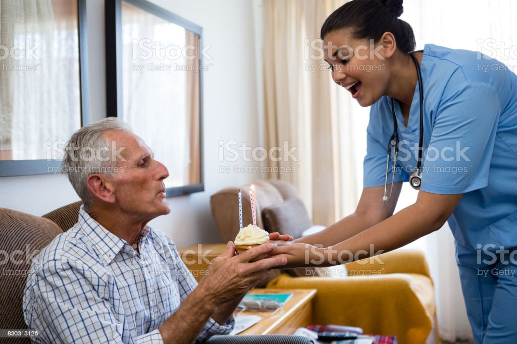 Senior Man Blowing Candles Of Cup Cake Being Held By Female Doctor Royalty Free Stock