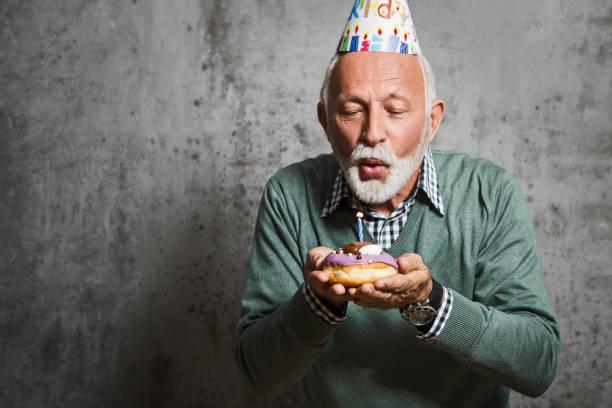 Senior Mann bläst Kerzen mit Geburtstagsmütze – Foto