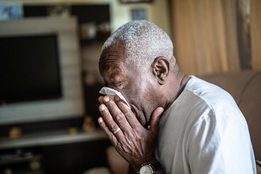 Senior man blowing his nose at home