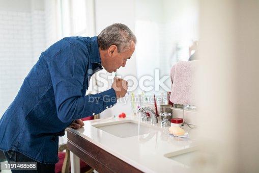 912658656 istock photo Senior man brushing his teeth in bathroom 1191468568