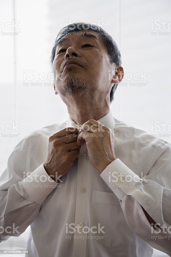 Senior man buttoning shirt collar, close-up royalty free stockfoto