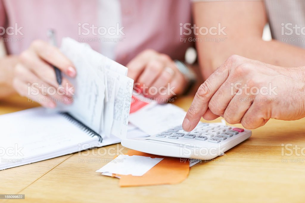 Senior man calculating expenses with woman royalty-free stock photo