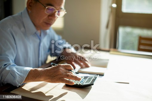 Taiwanese senior man sitting at table and calculating finances