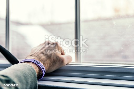 A senior adult man cancer patient - about to start a three month chemotherapy regimen - is clenching his fist with his hand resting on a window sill - looking out toward the blurry and indistinct future outside the window. He is wearing a generic cancer themed wristband (personally