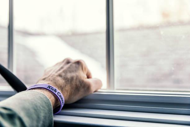senior woman krebspatient geballten faust armband hand - überleben stock-fotos und bilder