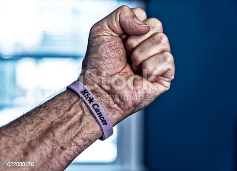 A senior adult man cancer patient about to start a three month chemotherapy regimen is reaching his hand up in the air and making a fist. He is wearing a generic cancer themed wristband with the embossed words