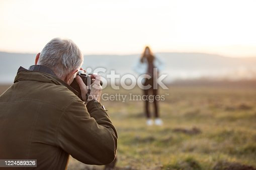 Senior Man Capturing an Image of Young Woman in Nature.