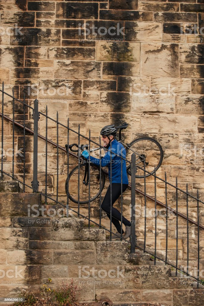 A Senior Man carries his Bicycle up Steps stock photo