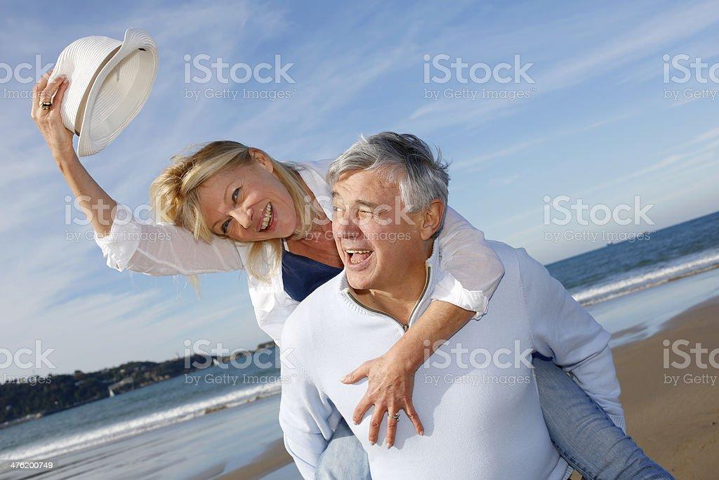 Senior man carrying wife on beach stock photo