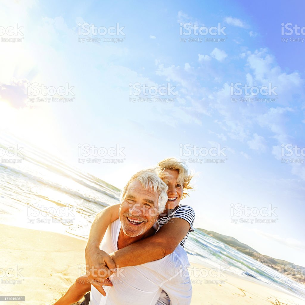 Senior man carrying wife on his back at the beach royalty-free stock photo