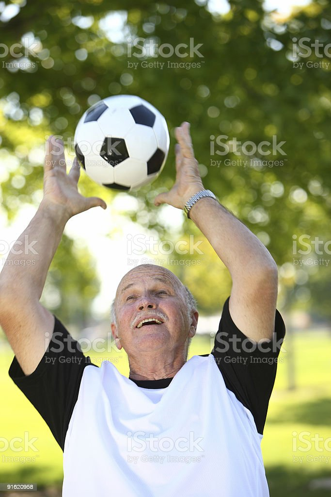 Senior man catching a soccer ball stock photo