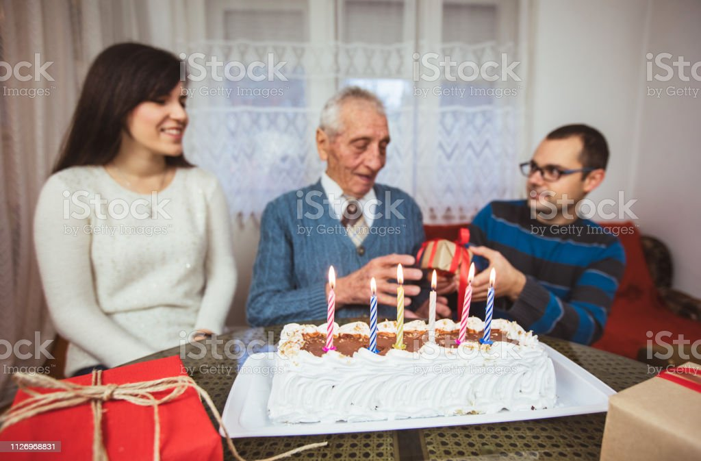 Senior man is receiving gift for his birthday from his grandchildren