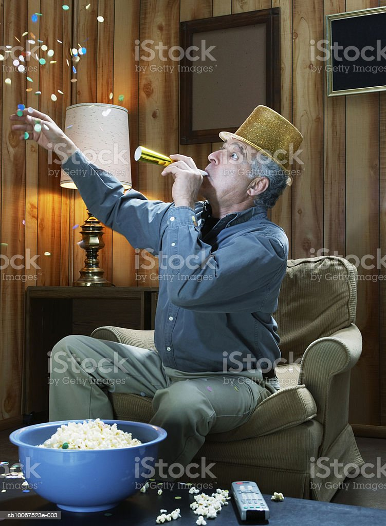 Senior man celebrating with party favors on New Years Eve royalty-free stock photo