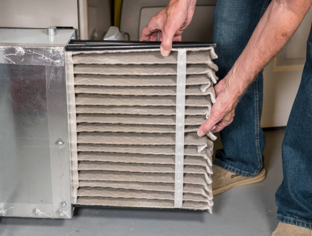 Senior man changing a dirty air filter in a HVAC Furnace Senior caucasian man changing a folded dirty air filter in the HVAC furnace system in basement of home air filter stock pictures, royalty-free photos & images