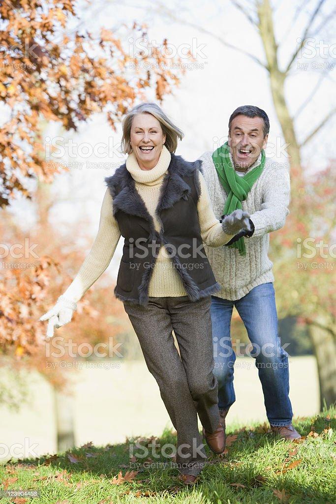 Senior man chasing woman through countryside royalty-free stock photo